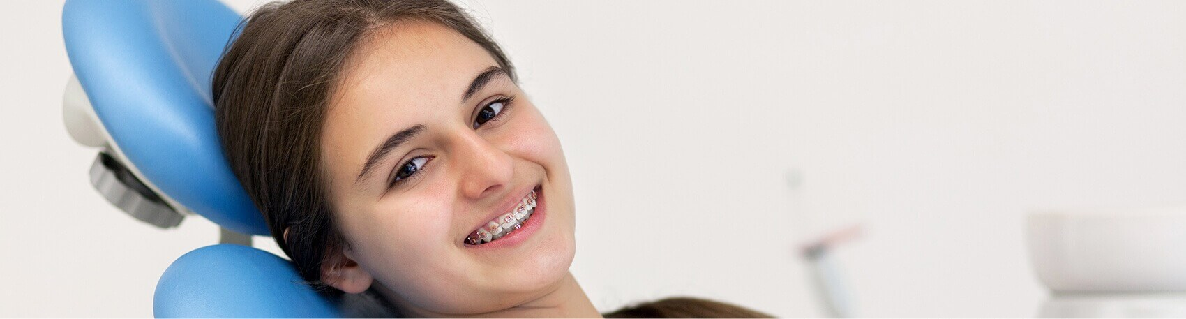 smiling girl with braces sitting in a dental chair