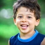 Smiling brunette little boy with unruly hair in a blue tanktop outside